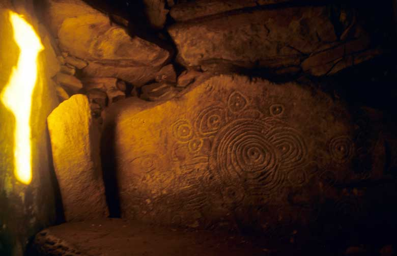 A sunbeam illuminates the art within the neolithic chamber of Cairn L.